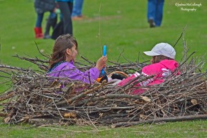 Image of two children sitting in a bird nest installation