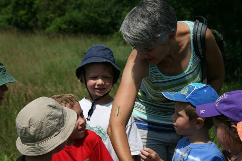 Sheila showing children an insect on her arm