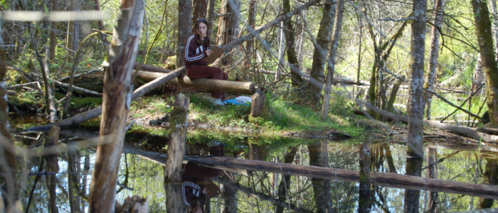 image of girl in park sitting on log