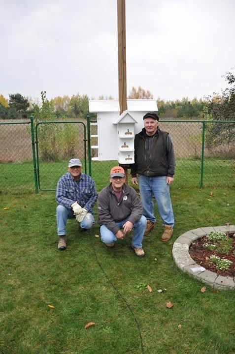 Image of members of Friends of the Sanctuary in front of a Purple Martin